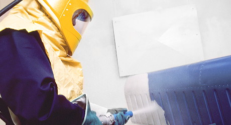 Image of a person working with sandblasting
